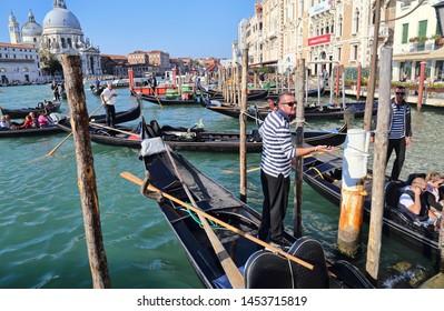 Venice, Italy - October 3, 2018: Gondolas and gondoliers on the Grand Canal at the Santa Maria della Salute church in Venice, Italy on October 3, 2018