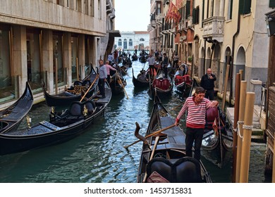 Venice, Italy - October 3 2018: Gondoliers and gondolas with tourists in a canal in Venice, Italy on October 3, 2018