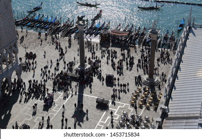 Venice, Italy - October 3, 2018: Tourists crowd around the columns on San Marco square at the waterfront with gondolas in Venice, Italy on October 3, 2018
