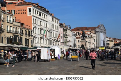 Venice, Italy - October 3, 2018: Tourists and gondolier walk along the waterfront of Venice, Italy on October 3, 2018