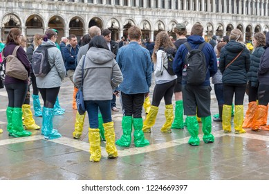 VENICE, ITALY- OCTOBER 30, 2018: Tourists in Piazza San Marco wearing rubber boots await the high water (acqua alta)