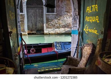 VENICE, ITALY - OCTOBER 7, 2018:  View of a venetian canal and a gondola, from the inside  of Libreria Alta Acqua Libreria, famous alternative bookshop in Venice, Italy. Romantic reading corner.