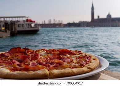 Venice, Italy pizza by the lagoon. Day view of pizza served on a dish with blurred background sea view.