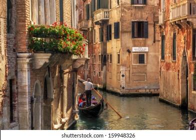 Venice, Italy. A romantic gondola floats on a narrow canal among old Venetian architecture