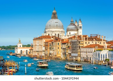 Venice, Italy. Scenic view of the Grand Canal with Basilica Santa Maria della Salute and tourist boats. Venice in the sunlight. Panorama of Venice in summer. Cityscape and landscape of sunny Venice.