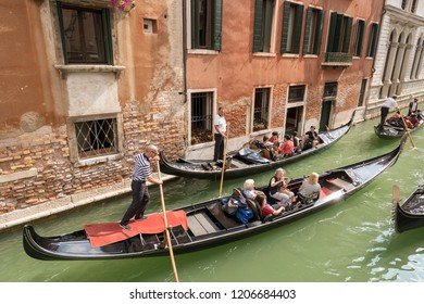 VENICE, ITALY, SEPT 13, 2015: Group of tourists sitting in the gondola with the gondolier, typical Venetian row boat. Sightseeing tour along the narrow canals of the famous city.