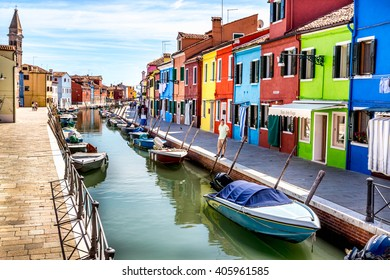 VENICE, ITALY - SEPTEMBER 02, 2013: Colorful old houses on the Island of Burano near Venice, Italy. Water canal with moored boats