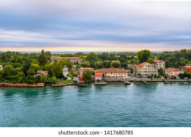 Venice, Italy - September 15 2018: Early morning view from a cruise ship on the Venetian Lagoon of the coast and waterfront homes, hotels and campgrounds on the island of Lido, Italy