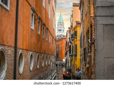 Venice, Italy - September 18 2018: Two Gondoliers carry tourists on gondolas in a narrow canal with the Bell Tower in view in Venice, Italy.