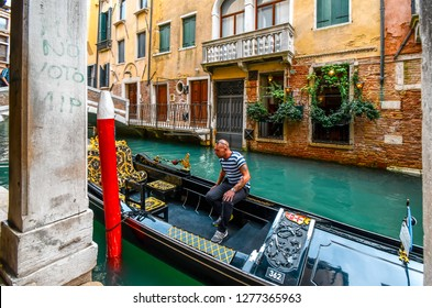 Venice, Italy - September 18 2018: A gondolier waits in his gondola for tourists on a picturesque canal in Venice, Italy