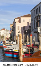 VENICE, ITALY - SEPTEMBER 20, 2017: Grand Canal, vintage buildings, parked boats at the marina. Canal Grande is one of the major water-traffic corridors in the city, it is 3.8 km long