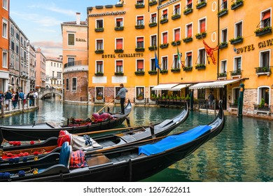 Venice, Italy - September 20 2018: A gondolier maneuvers his gondola in the gondola dock in the Orseolo Basin in front of a luxury hotel as tourists enjoy a late afternoon in Venice, Italy