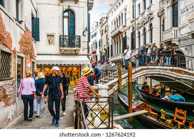 Venice, Italy - September 20 2018: A busy section of canal at the calle de la canonica as tourists cross the bridge over gondolas filled with tourists and a gondolier waits for customers in Venice.