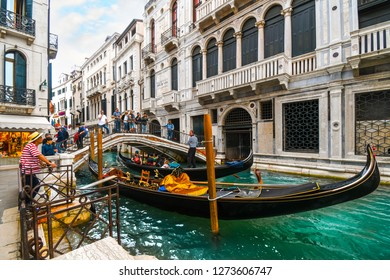 Venice, Italy - September 20 2018: A busy section of canal at the calle de la canonica as tourists cross the bridge over gondola and a gondolier waits for customers in Venice, Italy