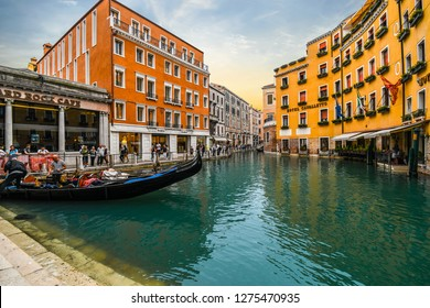 Venice, Italy - September 20 2018: A gondolier waits for customers i his gondola in the gondola dock in the Orseolo Basin in front of a luxury hotel as tourists enjoy a late afternoon in Venice, Italy