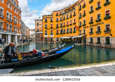 Venice, Italy - September 20 2018: A gondolier waits for customers in his gondola in the gondola dock in the Orseolo Basin in front of a luxury hotel as tourists enjoy an afternoon in Venice, Italy