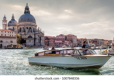 VENICE, ITALY - SEPTEMBER 21, 2012: Water taxi is sailing along the Grand Canal with Santa Maria della Salute church in background on 21 September 2012 in Venice, Italy.