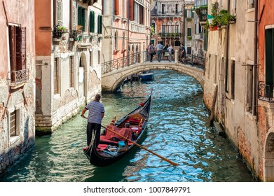 VENICE, ITALY - SEPTEMBER 21, 2012: Gondolier navigate gondola with tourists on the canal on 21 September 2012 in Venice, Italy. A gondolier is a Venetian boatman who propels a gondola.