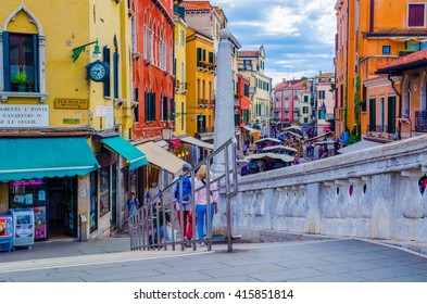 VENICE, ITALY, SEPTEMBER 21, 2015: crowds of tourists are passing through busy rio tera farsetti street which is full of restaurants and fruit vending stalls.