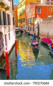 VENICE, ITALY -  SEPTEMBER 21, 2017   Gondola Tourists Colorful Small Canal Bridge Buildings Boats Reflections Venice Italy