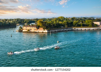 Venice, Italy - September 22 2018: A group of small motor boats cruise past one of the outlying islands near Poveglia, in the waters off of Venice, Italy.