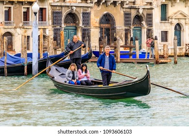 Venice, Italy - September 23, 2017: Gondoliers in traditional stripped shirt rowing a traghetto, cheaper alternative to a gondola, with passengers crossing Grand Canal