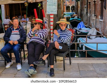 Venice, Italy - September 25, 2017: Gondoliers dressed in traditional stripped shirts and straw hats waiting for gondola passengers