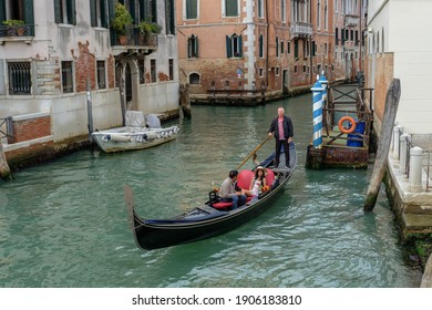 Venice, Italy; September 25 2019: Venetian gondolier with tourists on gondola. A ride on the Canal. Iconic cityscape.