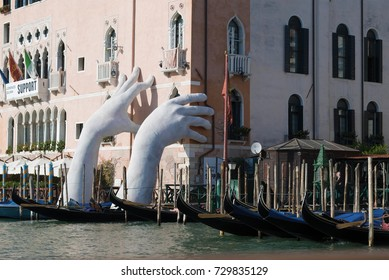 VENICE, ITALY - SEPTEMBER 26, 2017: Hands supporting the corner of the house. Modern sculpture on the Grand Canal
