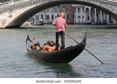 Venice, Italy - September 27, 2009: Tourists in Gondola Under Rialto Bridge at Grand Canal in Venezia, Italy.