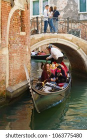 VENICE, ITALY - SEPTEMBER 28, 2017: Gondola with merry tourists swims under a low romantic bridge