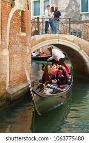 VENICE, ITALY - SEPTEMBER 28, 2017: Gondola with merry tourists swims under a low romantic bridge