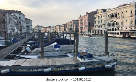 Venice, Italy - September 28, 2017: Wooden boats in front of the famous old buildings and palazzos along the Canale Grande in Venice, Italy.