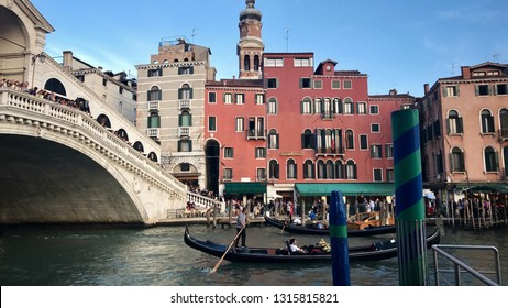 Venice, Italy - September 28, 2017: Gondolier with tourists and other boats on the Canale Grande in front of the famous Rialto Bridge of Venice, Italy.