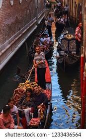 Venice, Italy - September 29, 2018: Tourists in gondolas in a canal in Venice, Italy on September 29, 2918