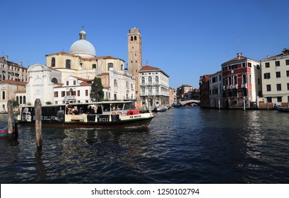 VENICE, ITALY - SEPTEMBER 29, 2018: Travelers on a ferry boat sail past the San Geremia church on the Canal Grande