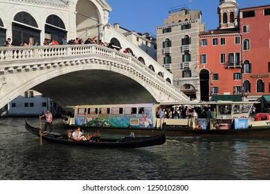 VENICE, ITALY - SEPTEMBER 29, 2018: Gondola and Vaporetto ferry boat on the Grand Canal at Rialto bridge