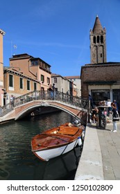 VENICE, ITALY - SEPTEMBER 29, 2018: Tourists take pictures along a canal on Campo San Barnaba square