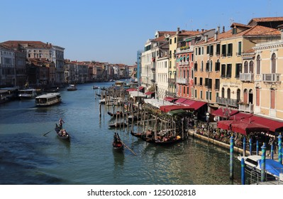 VENICE, ITALY - SEPTEMBER 29, 2018: Historical buildings with hotels and restaurants and boats and gondolas on the Canal Grande