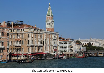 VENICE, ITALY - SEPTEMBER 29, 2018: Tower of San Marco and gondolas on the waterfront in