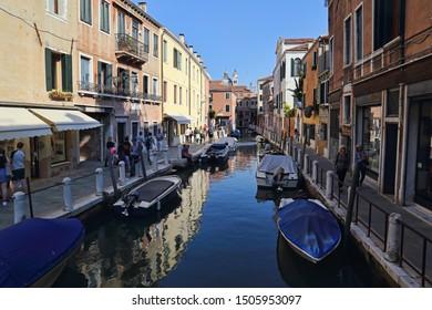Venice, Italy - September 29, 2018: Tourists walk along a canal in Venice, Italy on September 29, 2918