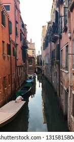 Venice, Italy - September 29,2017: Gondolier with tourists and gondola in the small canals between the famous old buildings of Venice, Italy.