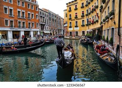 Venice, Italy - September 30, 2018: Gondolier and gondolas and tourists in Venice, Italy on September 30, 2918