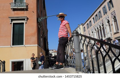 Venice, Italy - September 30, 2018: Gondolier in traditional dress stands on a bridge in Venice, Italy on September 30, 2918