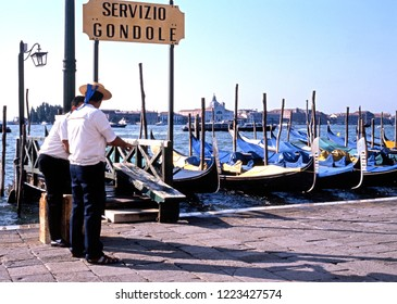VENICE, ITALY - SEPTEMBER 7, 1992 - Gondoliers standing on the waterfront by their Gondolas along the Grand Canal, Venice, Veneto, Italy, Europe, September 7, 1992.