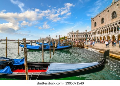 Venice, Italy - September 9 2018: Empty gondolas line the Grand Canal Gondola station as tourists pass by the Doge's Palace and St. Mark's Square with the Santa Maria Della Salute dome in the distance