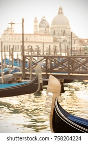 Venice, Italy: a traditional gondola (only prow visible) with Salute Basilica blurred on background.