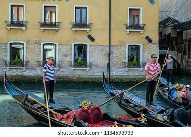 Venice, Italy-20 June, 2018: Gondolas with tourists, gondolier