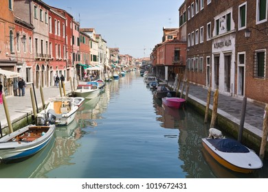 Venice, Italy-April 7, 2011: Motorboats moored along the centarl water street filled with tourists, island Burano, Italy