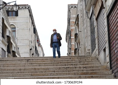 Venice, Italy-May 10, 2020:Elderly man in protective medical mask on the Rialto bridge in Venice. Coronavirus elderly advice. Safety old men. A concept of the danger of coronavirus for the elderly.